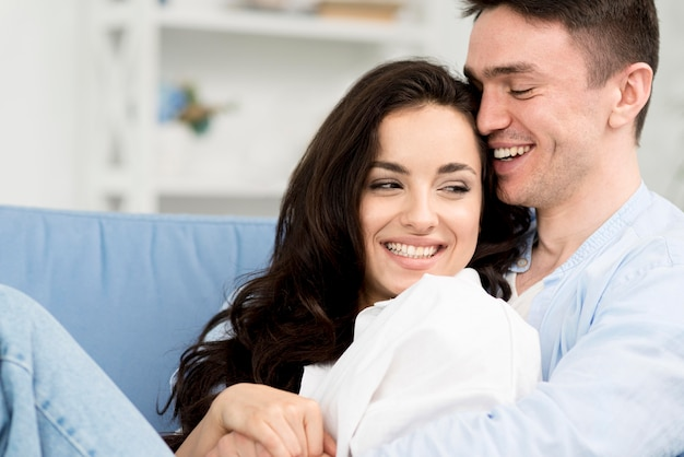 Side view of romantic and happy couple on sofa at home