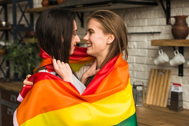 Side view of romantic lesbian young couple wrapped in lbgt flag