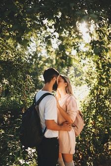 Side view of romantic young couple with backpack standing in green sunny garden and kissing happily