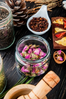 Side view of rose buds in a glass jar, dry black tea leaves, clove spice and chocolate bar with fruits on black wood