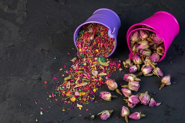 Vista laterale del tè rosa e petali di fiori secchi sparsi da piccoli secchi sul nero