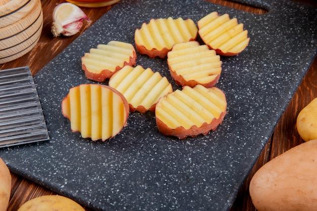 Vista laterale delle fette arruffate di patata sul tagliere con interi e aglio intorno sulla tavola di legno