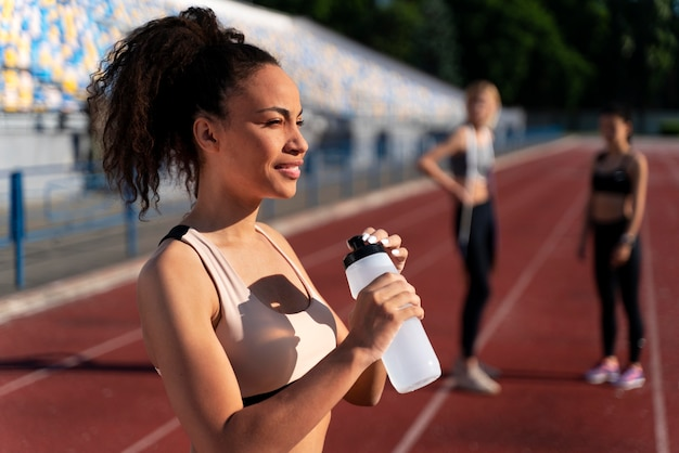 Side view runner holding a bottle of water