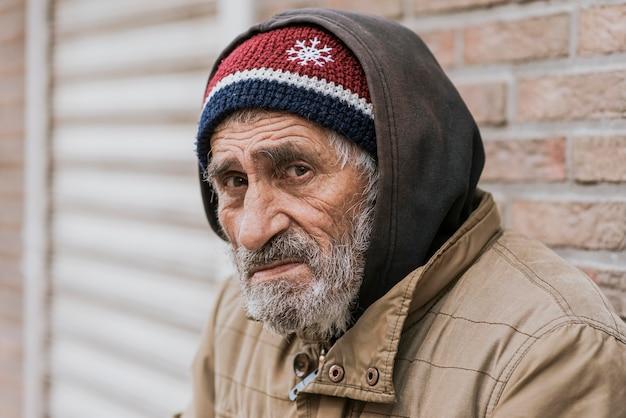 Vista laterale del barbuto triste senzatetto