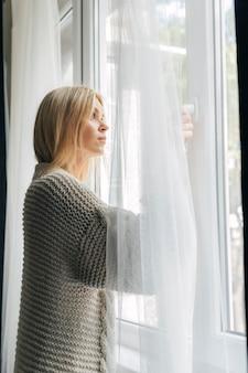 Vista laterale della donna triste a casa durante la pandemia guardando attraverso la finestra
