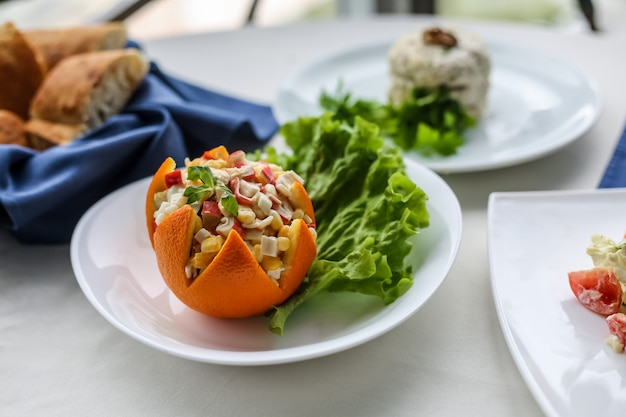 Side view salad in orange peel with a leaf of lettuce on a plate