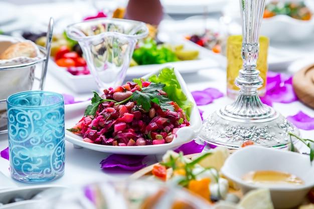ガラスのパンとテーブルのスナックを添えたテーブルのサイドビューサラダヴィネグレット