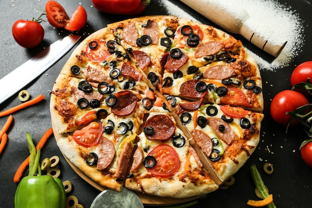 Side view salami pizza with bell pepper tomatoes olives and rolling pin with flour