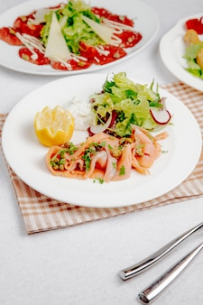 Side view of salmon carpaccio with lemon and fresh salad on the table