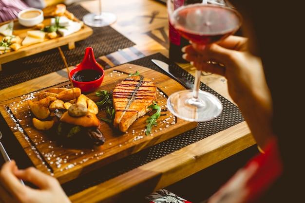 Вид сбоку стейк из лосося с картофелем в деревенском гранатовом соусе соль и бокал вина на столе
