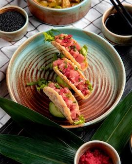Vista laterale dei taci di color salmone con caviale rosso e cipolla verde su un piatto