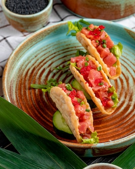 Side view of salmon tacos with red caviar and green onion on a plate