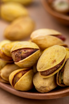 Side view of salted roasted pistachios on wooden spoon