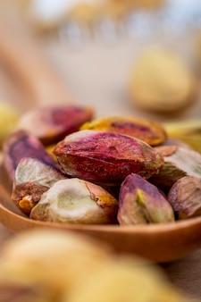Vista laterale dei pistacchi arrostiti salati sul cucchiaio di legno