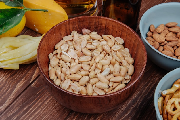 Side view of salty snack crispy peanuts in a wood bowl and cheese with beer on rustic