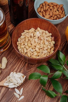 Side view of salty snacks peanuts in a wood bowl with almond and a mug of beer on rustic wood