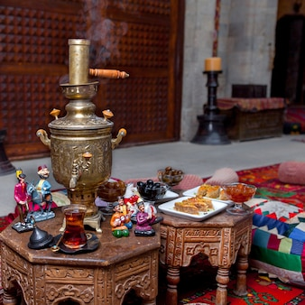 Боковой вид самовара со стаканом чая и статуэтками и пахлава в столике в ресторане