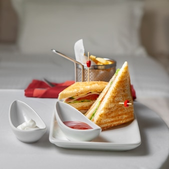 Side view sandwich in a plate with french fries, ketchup in bedroom