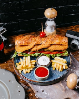 Side view of sandwich with chicken nuggets salad leaves pickles and sauce served with french fries on wooden table