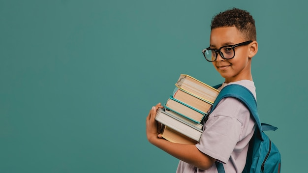Side view school boy holding a pile of books copy space