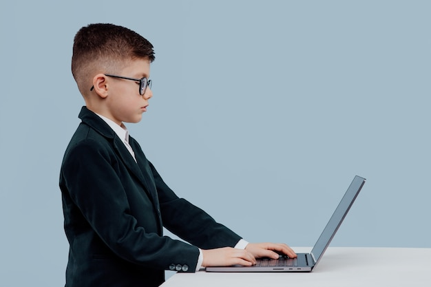 Side view schoolboy with glasses using a laptop little boss in office funny kid isolated on blue bac...