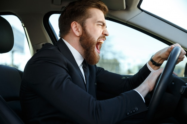 Side view of screaming business man driving and beeps