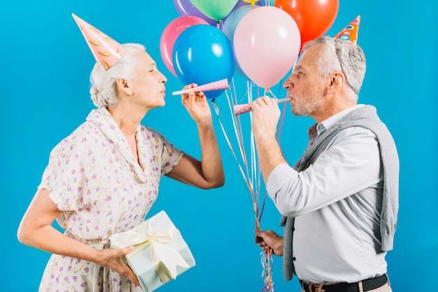 Side view of senior couple looking at each other blowing party horn on blue backdrop