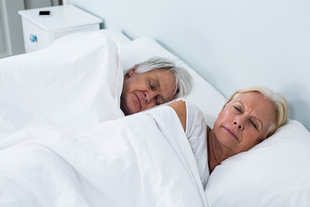 Side view of senior couple sleeping on bed
