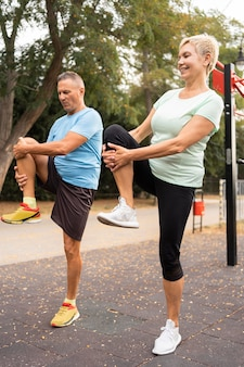 Side view of senior couple warming up before exercising outdoors