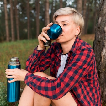 Side view of senior tourist woman drinking out of thermos