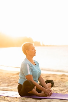 Vista laterale della donna senior che fa yoga sulla spiaggia
