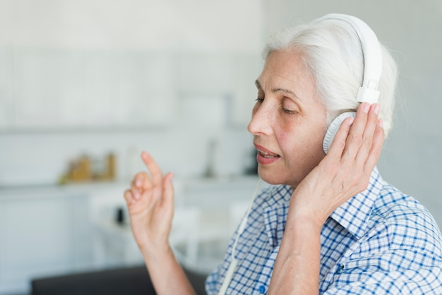 Side view of senior woman listening music on headphone singing