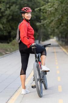 Vista laterale della donna senior all'aperto equitazione bicicletta