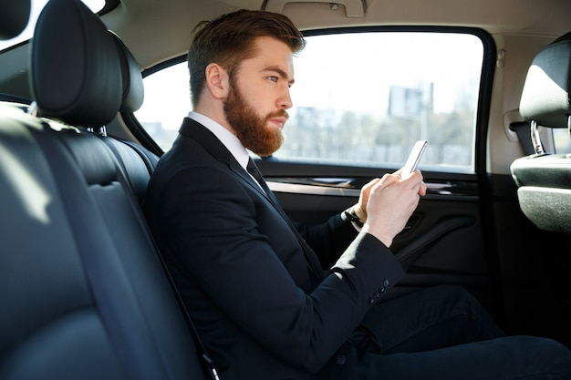 Side view of serious bearded business man holding smartphone