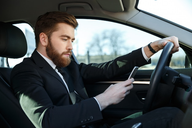 Side view of serious business man using phone at wheel