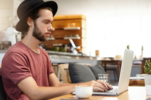 Side view of serious and concentrated bearded freelancer in black headwear keyboarding on laptop pc, working remotely, using free high-speed internet connection during breakfast at modern cafe
