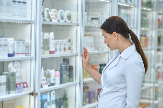Side view of a serious druggist in a white robe standing before the pharmacy display cabinet