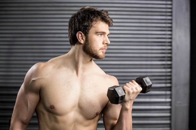 Side view of serious man lifting weight at gym