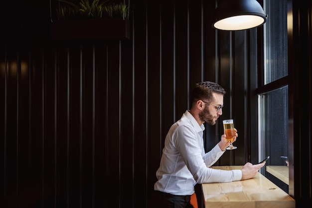 Side view of serious man in shirt sitting in pub next to window, using smart phone for replying messages and holding glass of beer.