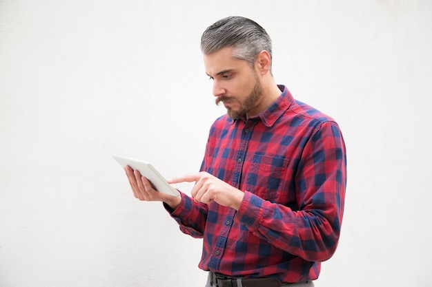 Side view of serious man using tablet pc