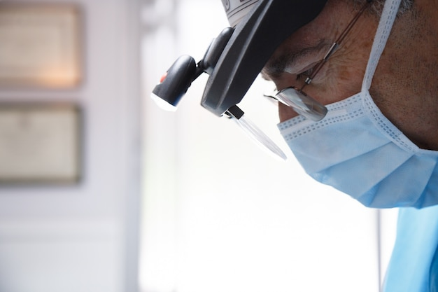 Side view of serious professional dentist wearing lighting glasses and working with concentration in clinic.