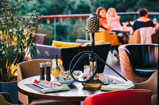 Side view served table with sushi and pineapple shisha