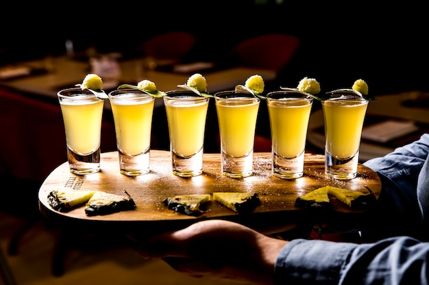 Side view of set of alcoholic cocktails in shot glasses with pineapple slices on wooden board on dark background