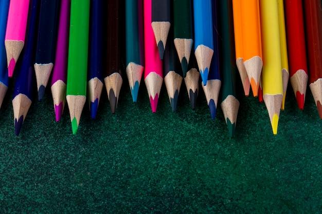 Vista laterale di un set di matite colorate su oscurità