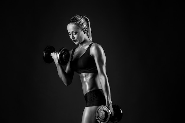 Side view of sexual muscular blonde with ponytail in bikini posing with dumbbells on black .