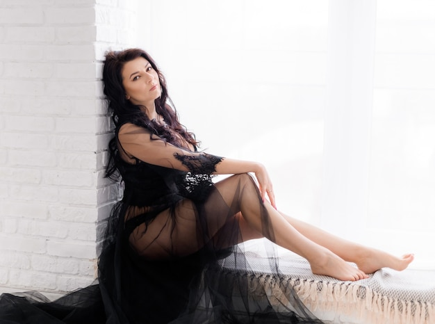 Side view of sexy brunette posing in a black transparent peignoir