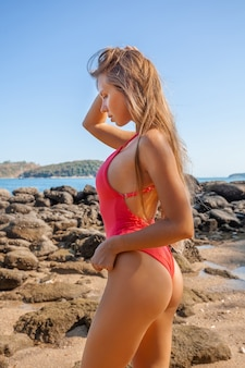 Side view of sexy young girl with long hair in red swimwear on beach with rocks.