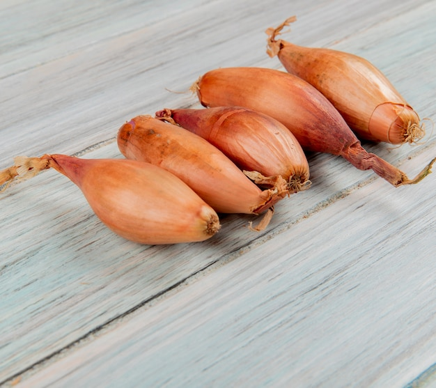 Side view of shallots on wooden background