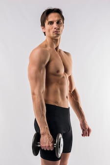 Side view of shirtless athletic man holding weight
