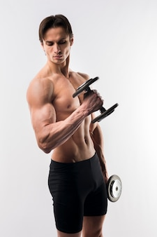 Side view of shirtless athletic man holding weights
